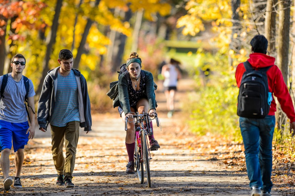 A student bikes on the lakeshore path in fall.