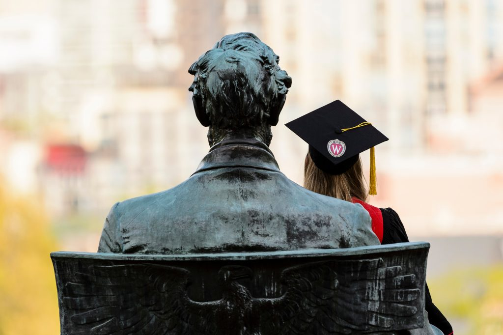 A soon-to-be graduate sits in the lap of the Abraham Lincoln statue